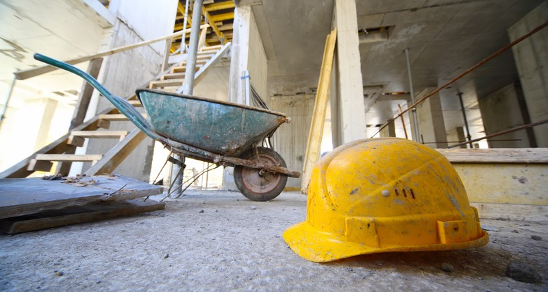 building site, hard hat and wheelbarrow