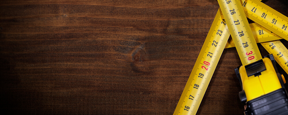 Tape Measures on Brown Wooden Background
