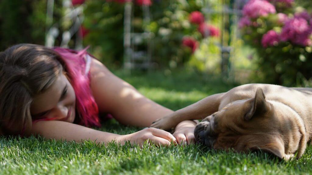 Girl laying with her dog in the garden